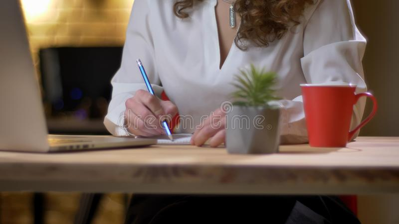 Portrait of hands of businesswoman writing on paper on office background. Portrait of hands of businesswoman writing on paper on office background royalty free stock images