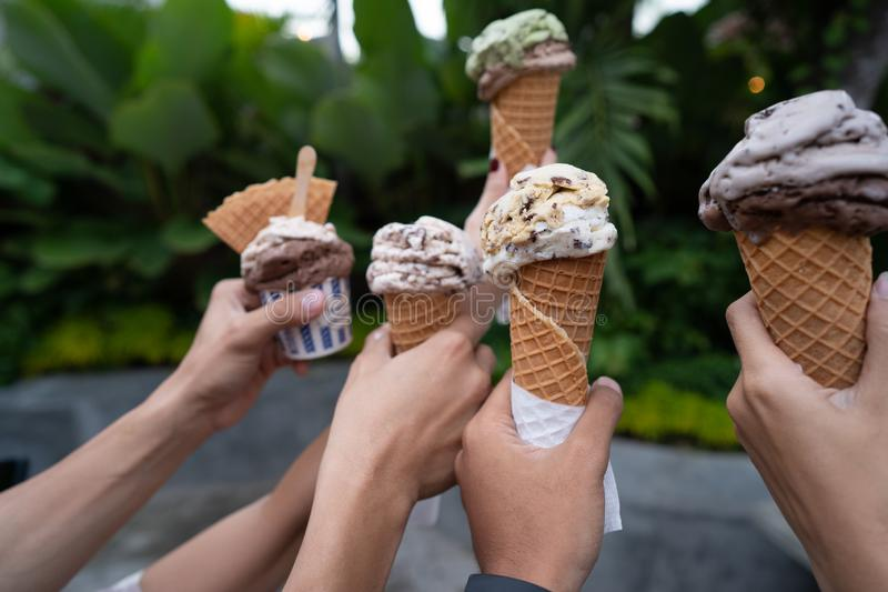 Portrait of hands holding ice cream cone background green trees stock images