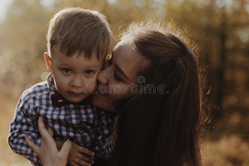 Portrait of handsom happy young boy with his mom. Mom is kissing his hands. Son is looking at the camera and smiling. The sun is shining from behind stock photo