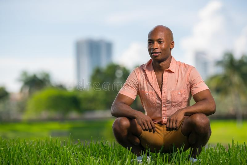 Portrait of handsome African American man in summer casual clothing. Squatting position and smiling off camera with blurry royalty free stock photos