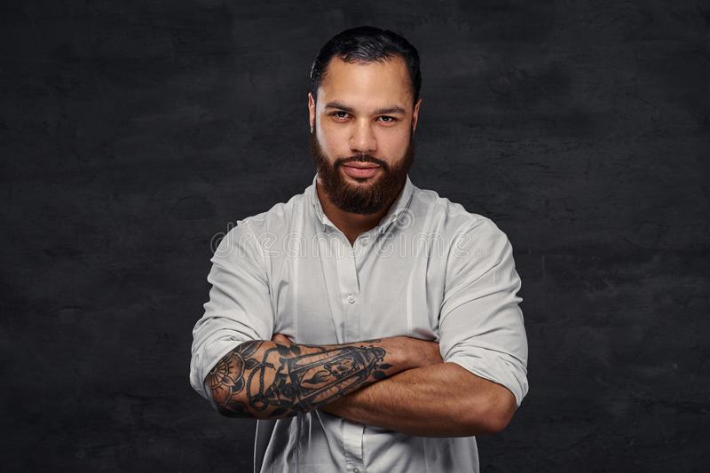 Portrait of a handsome African-American tattooed man with stylish hair and beard, stands with crossed arms. royalty free stock photography