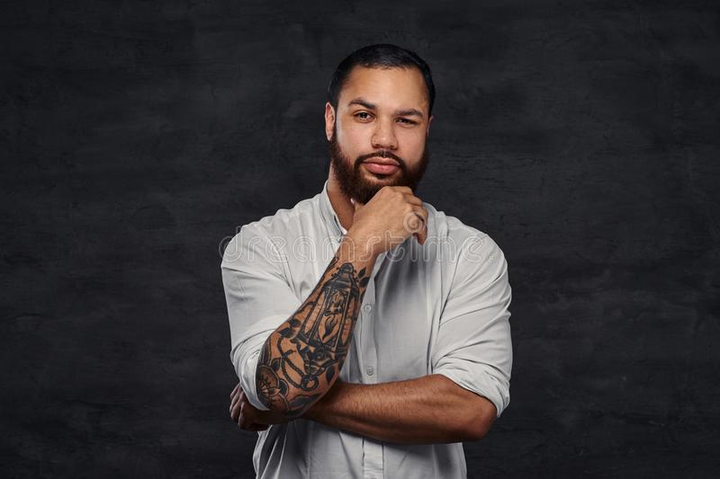 Portrait of a handsome African-American tattooed man with stylish hair and beard in a white shirt, holding hand on his stock images