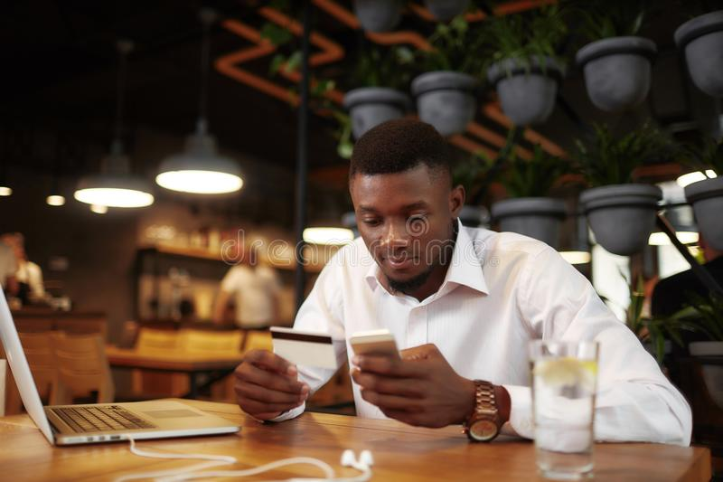 African man pay with card in cafe using call phone. stock photo
