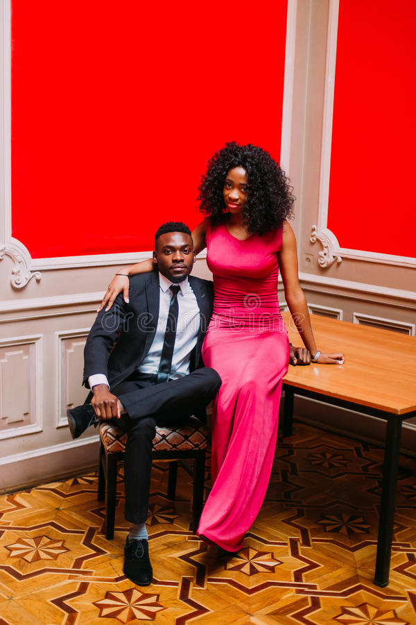 Portrait of handsome afro american businessman and beautiful african woman with red dress. Young couple hugging in the royalty free stock images