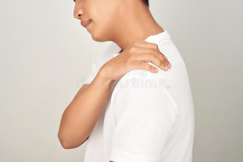 Portrait of handsome Asian man with uncomfortable face, suffering from neck pain. Medical and healthcare concept on white stock images