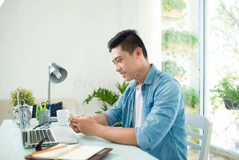 Portrait of handsome asian young business man holding mobile phone and working on laptop computer at office desk stock image