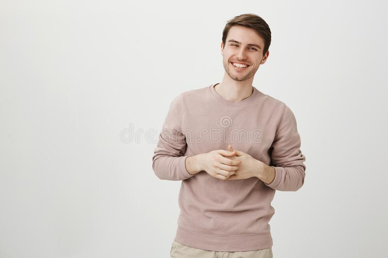 Portrait of handsome athletic male with charming smile holding hands near chest, standing in casual post as if talking. Over gray background. Seductive man stock images