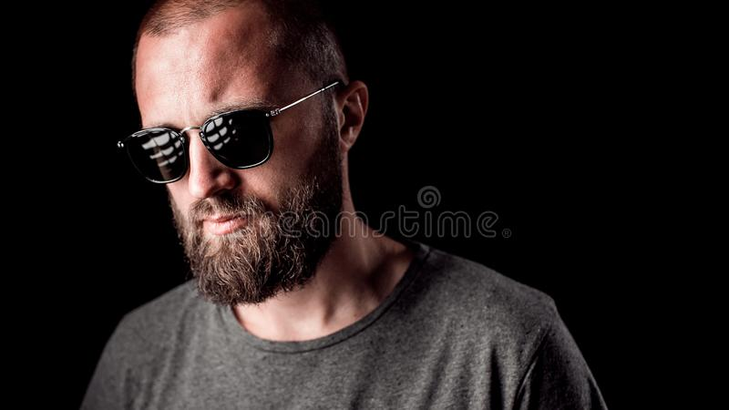 Portrait of a handsome balded man with long well trimmed beard wearing sunglasses and grey shirt stock images