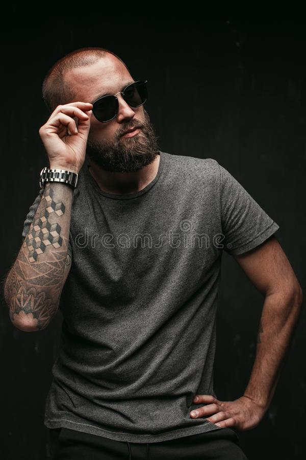 Portrait of a handsome balded man with long well trimmed beard wearing sunglasses and grey shirt looking away to side royalty free stock photos