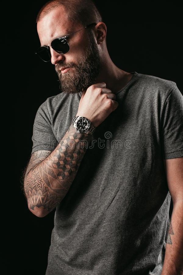 Portrait of a handsome balded man with long well trimmed beard wearing sunglasses and grey shirt royalty free stock photo