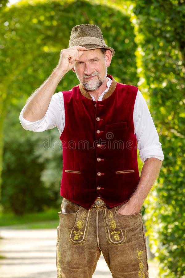 Handsome bavarian man in his 50s standing outdoors in park stock photography