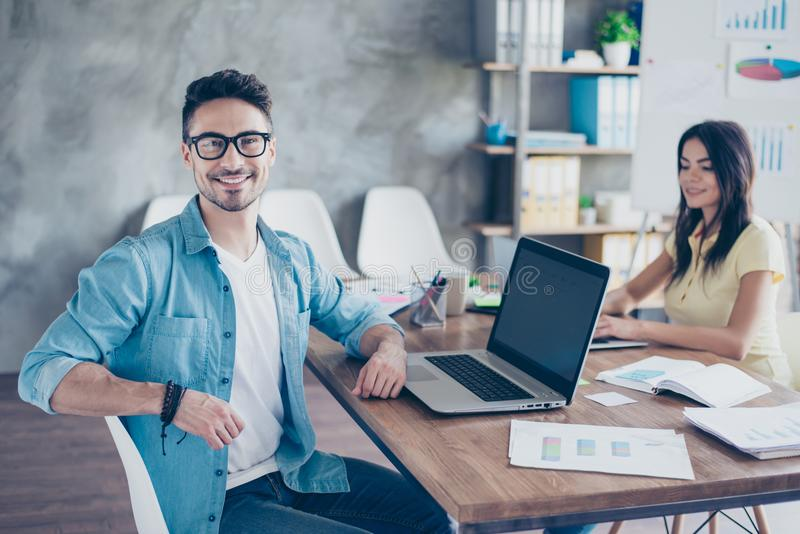 Portrait of handsome bearded attractive young businessman in glasses sitting at his desktop and smiling at camera in open space o stock photography