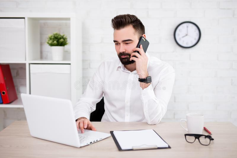Portrait of handsome bearded businessman using computer and talking by phone in office royalty free stock images