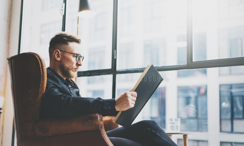 Portrait handsome bearded businessman wearing glasses,black shirt.Man sitting in vintage chair modern loft studio, reading book an. Portrait handsome bearded stock photography