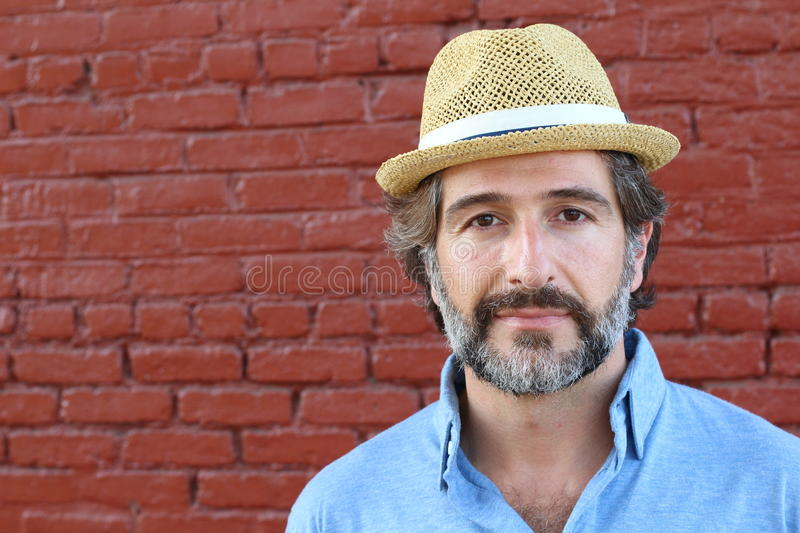 Portrait of handsome bearded man in hat on red background royalty free stock photos