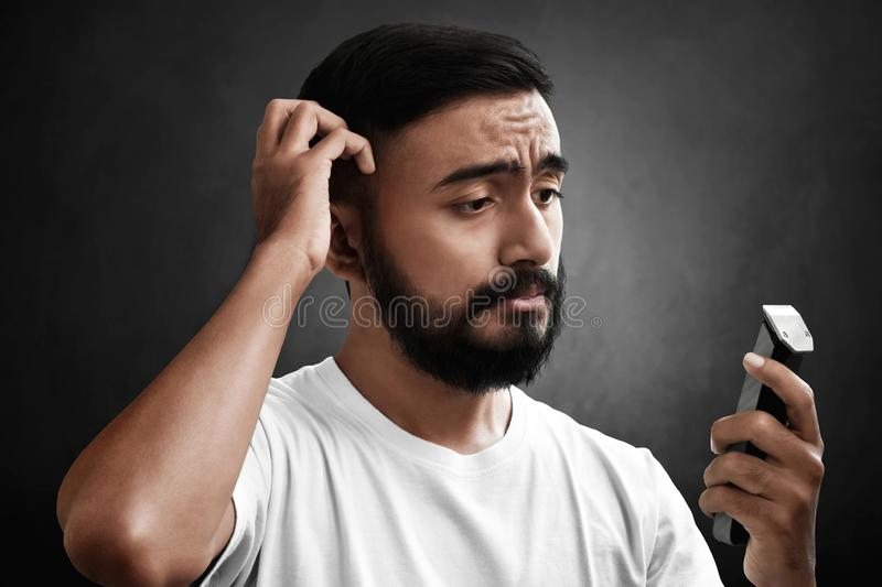 Portrait of handsome bearded man holding electric razor royalty free stock photo