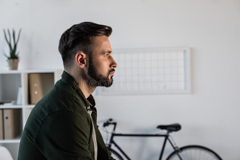Portrait of handsome bearded man looking away in office stock photo