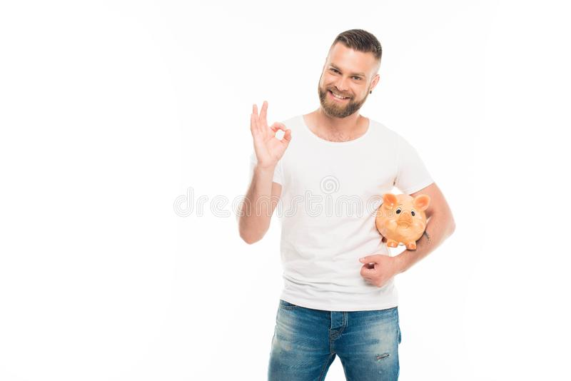 Portrait of handsome bearded man with piggy bank showing ok sign, stock photo