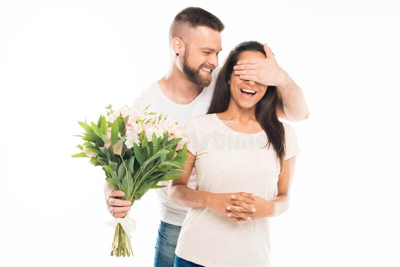 portrait of handsome bearded man with bouquet of flowers covering his girlfriends eyes, stock photos