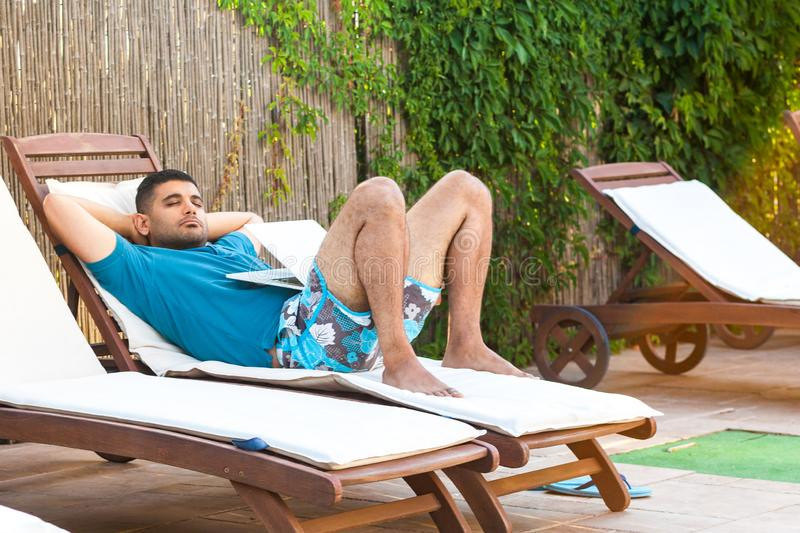 Portrait of handsome bearded young adult freelancer man in blue t-shirt and shorts lying on cozysunbed with laptop and sleep after royalty free stock image