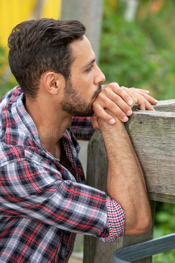 Handsome bearded young man sitting outdoors. Portrait of handsome bearded young man outdoors royalty free stock photography