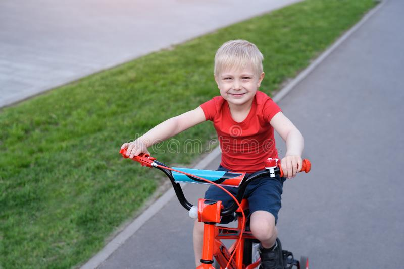 Portrait of a handsome blond boy rides on a children`s bicycle. Urban background.  royalty free stock image