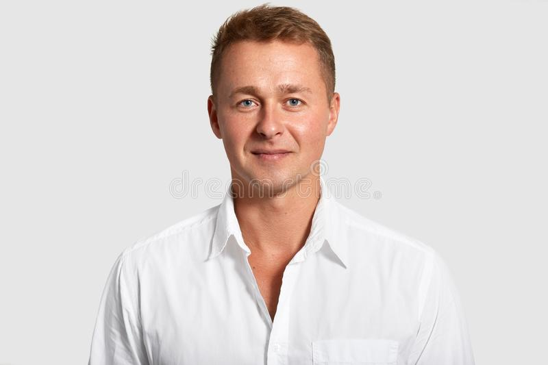 Portrait of handsome blue eyed man with confident expression, wears white shirt, looks at camera, being prosperous businessman, royalty free stock images