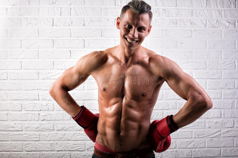 Portrait of handsome boxer man standing on the bric wall and looking at camera with intense gaze. Portrait of handsome boxer man standing on the wall and looking stock photography