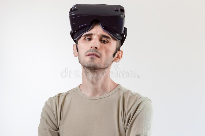 Portrait of a handsome brunet man with virtual reality goggles on head on white background royalty free stock photography