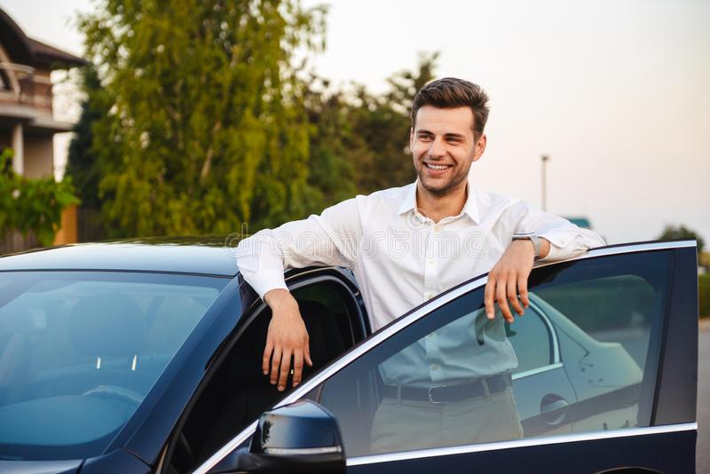 Portrait of handsome businesslike man wearing suit, standing nea. Portrait of handsome businesslike man wearing suit standing near his luxury black car with open royalty free stock image