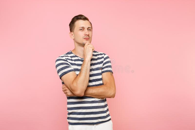 Portrait of handsome businesslike pensive young man in striped t-shirt put hand on chin copy space isolated on trending royalty free stock photos