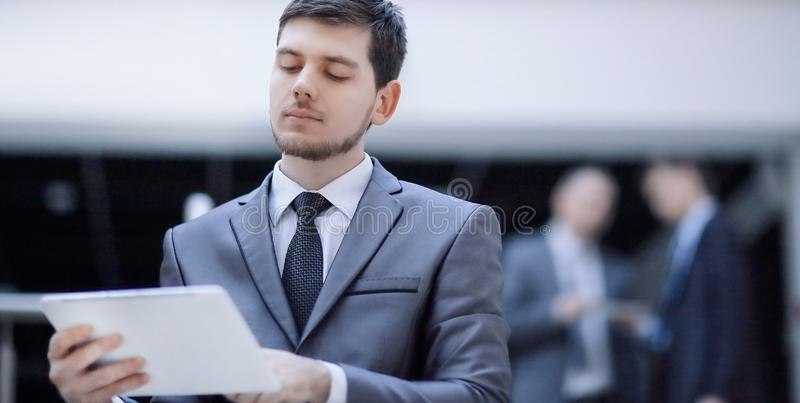 Portrait of handsome businessman on blurred office background royalty free stock image