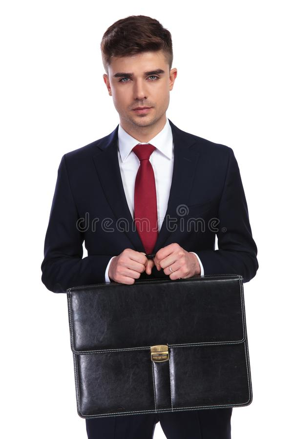 Portrait of handsome businessman holding briefcase with both han stock image