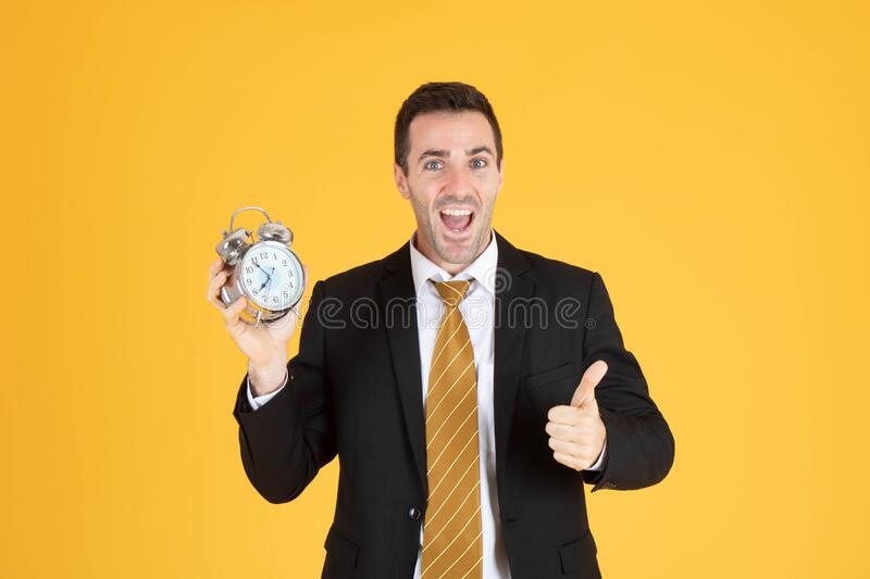 Portrait of a handsome businessman holding clock with thumbs up. On yellow background royalty free stock image