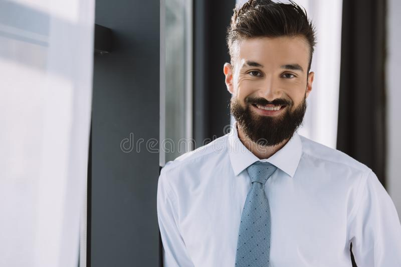 portrait of handsome businessman standing near window royalty free stock photography