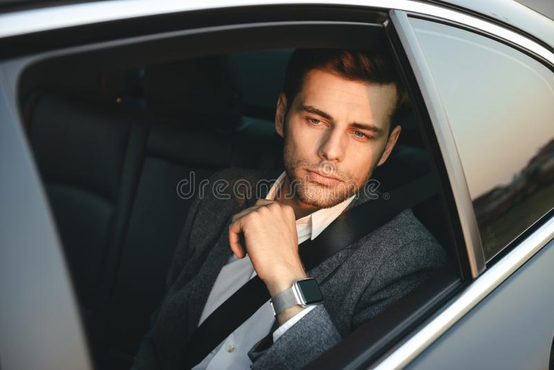 Portrait of handsome caucasian man wearing businesslike suit, ba. Portrait of handsome caucasian man wearing businesslike suit back sitting while riding in car royalty free stock photos