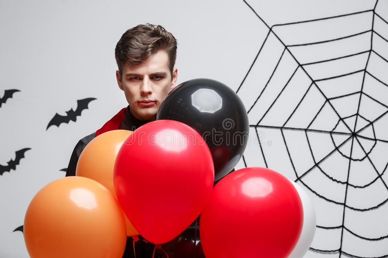 Portrait of handsome caucasian in Vampire halloween costume with colorful Balloon. royalty free stock image