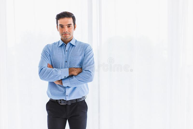Portrait of a handsome Caucasian young businessman standing arms crossed, smiling in the office and looking at the camera on a stock image