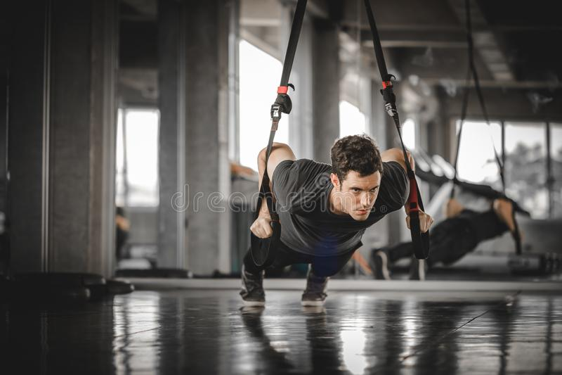 Portrait handsome caucasian young man healthy fitness doing push up at indoor workout in gym. stock photography
