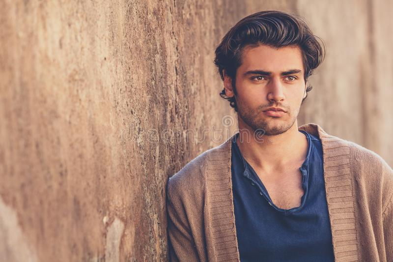 Portrait of handsome and charming young man. He is leaning against an outdoor wall. royalty free stock image