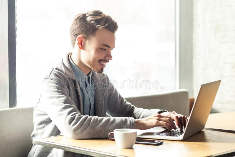 Portrait of handsome cheerful bearded young businessman in grey blazer are sitting in cafe and typing message with toothy smile stock images