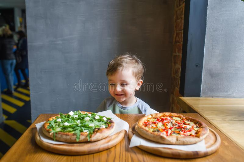 A portrait of handsome child eating pizza in cosy cafe royalty free stock image