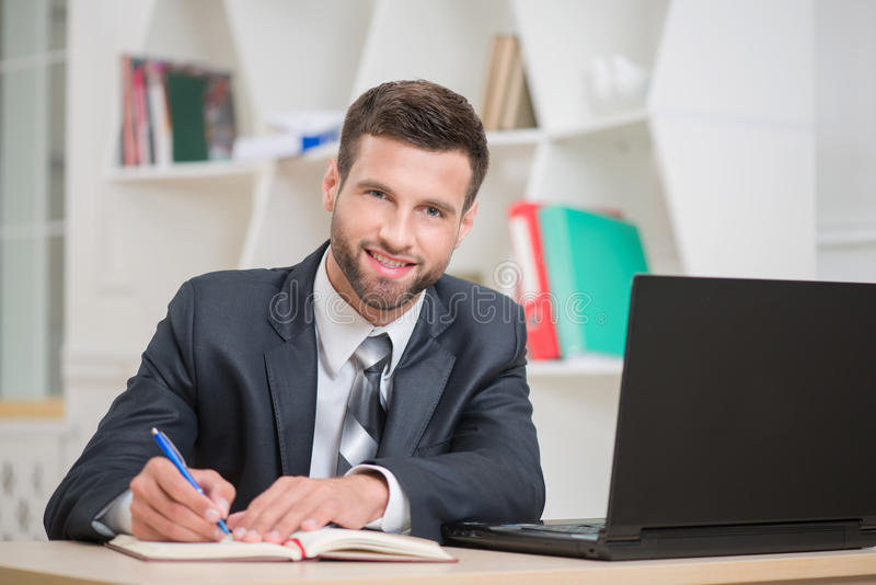 Portrait of handsome confident businessman writing stock photo