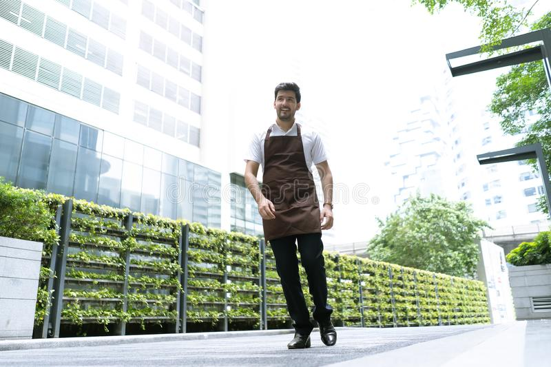 Portrait of a handsome and confident cafe owner standing waitress in brown apron walking in around his coffee shop.Small Business stock image
