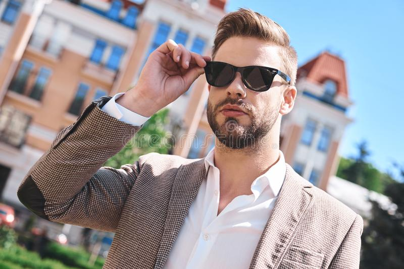 Portrait of a handsome elegant young man, model of fashion, wearing tinted sunglasses in urban background royalty free stock photography