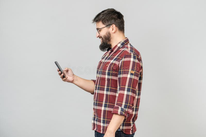 Portrait of handsome european man holding telephone while texting royalty free stock photography
