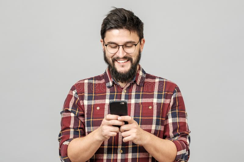 Portrait of handsome european man holding telephone while texting stock photography