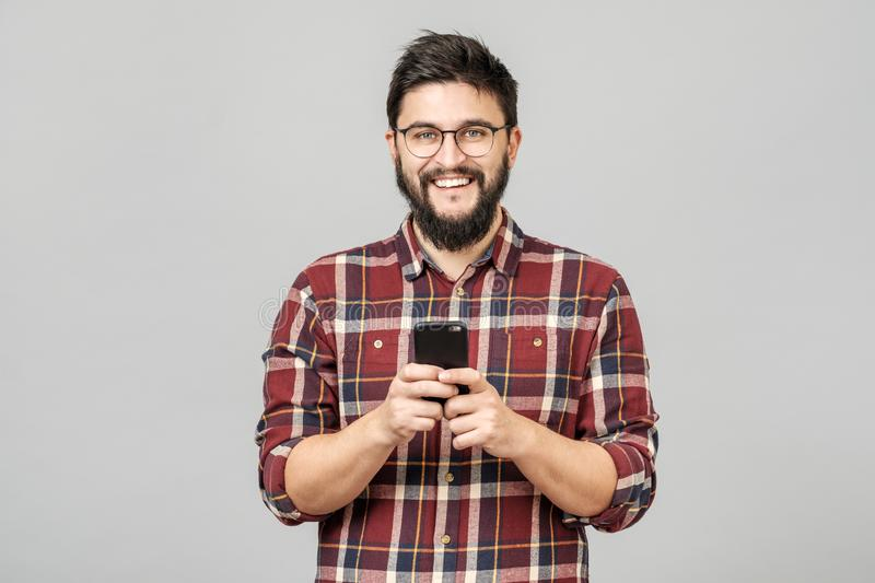 Portrait of handsome european man holding telephone while texting stock images