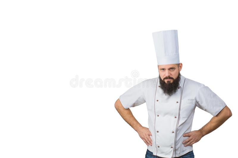 Portrait of handsome evil male chef in uniform hands on waist isolated on white background, copy space on side. royalty free stock photography