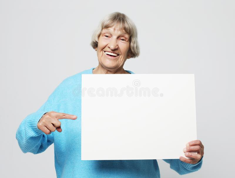 Portrait of handsome expressive grandmother in light blue sweater. Indoor,studio shot, isolated on gray background stock photos